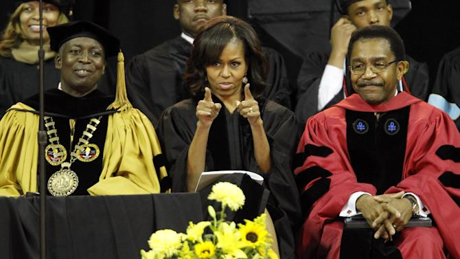 First lady Michelle Obama points to the students as she sits with Bowie State University President Dr. Mickey L. Burnim, left, and Provost Dr. Weldon Jackson, right,  at the commencement ceremony for Bowie State University, Friday, May 17, 2013, at the University of Maryland in College Park, Md. (AP Photo/Ann Heisenfelt)