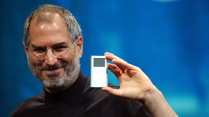 FILE - In this Jan. 6, 2004 file photo, Apple CEO Steve Jobs displays the iPod mini at the Macworld Conference and Expo in San Francisco. Jobs, the Apple founder and former CEO who invented and masterfully marketed ever-sleeker gadgets that transformed everyday technology, from the personal computer to the iPod and iPhone, died Wednesday. He was 56. (AP Photo/Marcio Jose Sanchez, File)