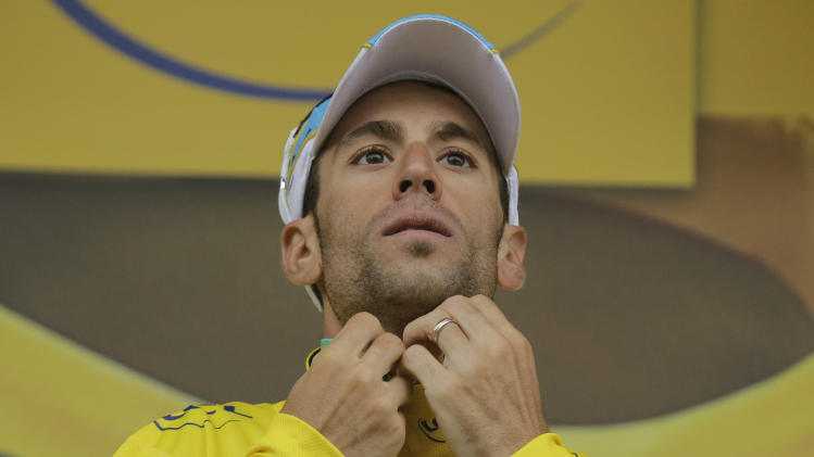 Italy's Vincenzo Nibali, wearing the overall leader's yellow jersey, adjusts the overall leader's yellow jersey on the podium of the eighth stage of the Tour de France cycling race over 161 kilometers (100 miles) with start in Tomblaine and finish in Gerardmer, France, Saturday, July 12, 2014. (AP Photo/Laurent Cipriani)