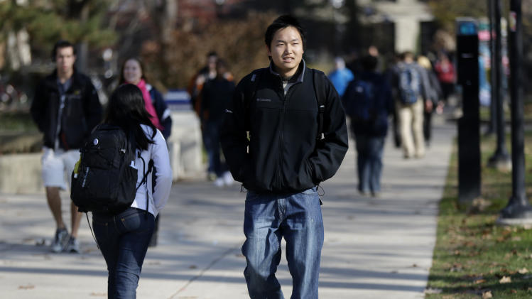 In this Friday, Nov. 9, 2012 photo, Kedao Wang, 21, of Shanghai, China, a senior at the University of Michigan walks on campus in Ann Arbor, Mich. Wang, one of about 6,400 overseas students at the University of Michigan, said his experience has been excellent but agrees growing numbers don't solve the isolation problem. Virtually all Chinese students struggle at least somewhat to fit in, due to language and cultural barriers. New figures out Monday, Nov. 12, 2012 show international enrollment at U.S. colleges and universities grew nearly 6 percent last year, driven by a 23-percent increase from China, even as total enrollment was leveling out. But perhaps more revealing is where much of the growth is concentrated: big, public land-grant colleges, notably in the Midwest. (AP Photo/Paul Sancya)