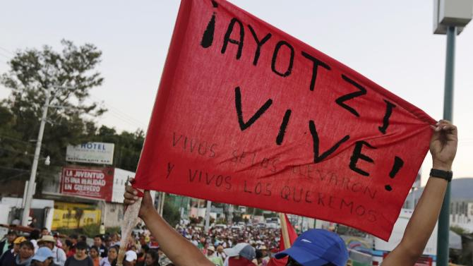 A masked student of Ayotzinapa Teacher Training College holds a banner as he walks with CETEG members during a march on outskirts of Chilpancingo