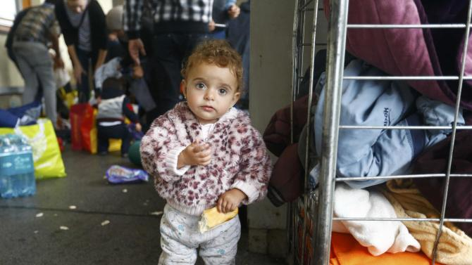 Young child eats bread as clothing is distributed to migrants at railway station in Vienna