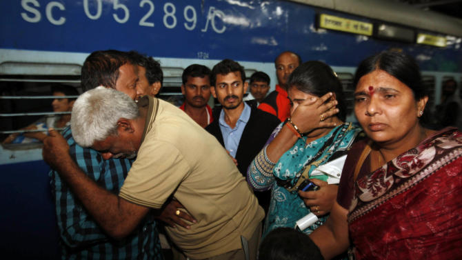 Indian pilgrim Rahava Chary, second from left, who was stranded after flash floods and landslides in Uttarakhand state, hugs his family members on his arrival in Hyderabad, India, Tuesday, June 25, 2013. An air force helicopter returning from a rescue mission in flood-ravaged northern India hit the side of a mountain and fell into a river on Tuesday, killing eight people, officials said. Bad weather has hampered rescue efforts in Uttarakhand state, where more than 1,000 people are believed to have died and thousands of others remain stranded in remote areas because of landslides and floods triggered by torrential monsoon rains. (AP Photo/Mahesh Kumar A.)