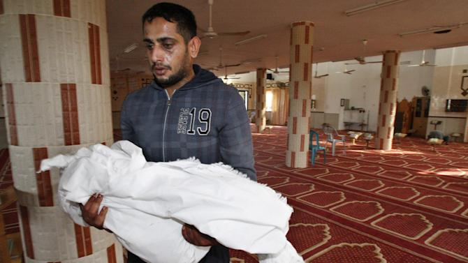 Palestinian Yoused Abu Khoussa, carries the body of his one and a half year-old son Iyad, during his funeral in Bureij Refugee Camp, central Gaza Strip, Sunday, Nov. 18, 2012. The baby boy was one of five Palestinian children killed in Israeli strikes on Sunday, according to a Gaza health official.(AP Photo/Adel Hana)