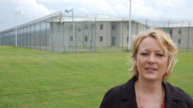 In this May 1, 2013, photo Arkansas Department of Correction spokeswoman Shea Wilson stands outside the Tucker Unit in Tucker, Ark. Since Lester Stiggers fled prison 43 years ago, the convicted killer has spent most of his life a free man in the Detroit area, thanks to a progressive governor who refused to send him back to Arkansas' then-infamous penitentiary system. (AP Photo/Jeannie Nuss)