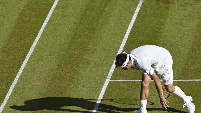 Kei Nishikori of Japan, wearing strapping on his calf, stumbles as he stretches for a shot during his match against Simone Bolelli of Italy at the Wimbledon Tennis Championships in London