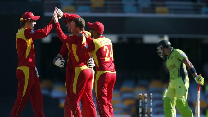 Pakistan's Umar Akmal reacts after he was bowled for 33 runs as Zimbabwe's Sean Williams celebrates with team mates during their Cricket World Cup match at the Gabba in Brisbane