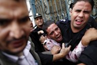 Egyptian police protect an opposition demonstrater after a scuffle with members of the Muslim Brotherhood and supporters of Egypt's Islamist President Mohamed Morsi during clashes outside the presidential palace in Cairo on December 5. Five demonstrators died overnight in the worst violence since Mohamed Morsi became Egypt's first Islamist president in June