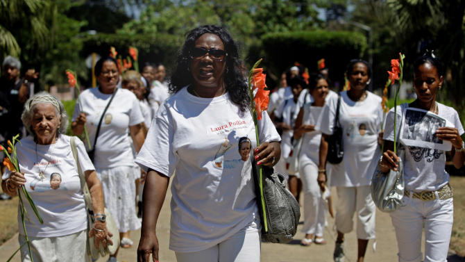 Berta Soler, center, leads the weekly march of the dissident group Ladies in White in front of Santa Rita church in Havana, Cuba, Sunday March 25, 2012. The Ladies in White held its customary weekly protest without incident a day before Pope Benedict XVI visits the island. (AP Photo/Franklin Reyes)