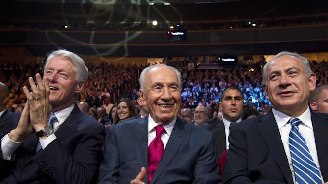 Israeli President Shimon Peres , center, sits flanked by former US President Bill Clinton and Israeli Prime Minister Benjamin Netanyahu, right, in a Jerusalem convention center as Peres' 90th birthday gala gets underway, Tuesday June 18 2013. (AP Photo/ Jim Hollander, pool)