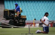 England's Monty Panesar stretches as groundsmen work on the pitch before a team training session at the Sydney Cricket Ground January 2, 2014. REUTERS/David Gray