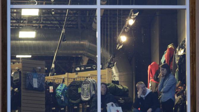 Mall workers and shoppers wait to be cleared to leave REI at Clackamas Town Center in Portland, Ore., where a shooting occurred Tuesday, Dec. 11, 2012. A gunman opened fire at the suburban Portland shopping mall Tuesday, killing two people and wounding another as people were doing their Christmas shopping, authorities said. (AP Photo/The Oregonian, Thomas Boyd)