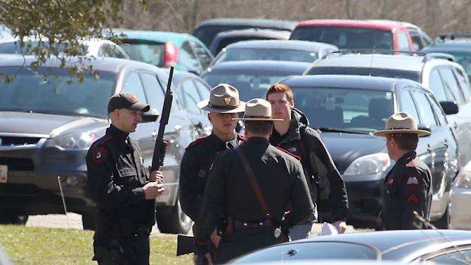 A Rhode Island State police officer holds a shotgun outside Chafee Hall on the campus of the University of Rhode Island after the school ordered a lockdown of the campus in South Kingstown, R.I., Thursday, April 4, 2013. An auditorium in Chafee Hall was evacuated after a report of an individual with a gun. (AP Photo/Stew Milne)