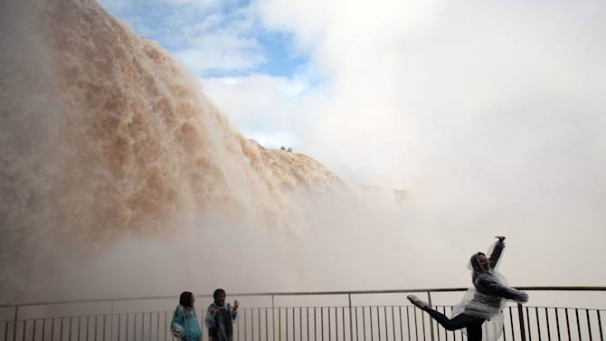 """Tourists pose for photos near the Iguazu Falls in Iguazu National Park in Foz Do Iguazu, Brazil, Thursday, June 27, 2013. Torrential rain in the past week in southern Brazil has swollen Iguazu River, obliging authorities to close some of the walkways that lead to the waterfalls known as """"Garganta del Diablo,"""" or Devil's Throat. (AP Photo/Jorge Saenz)"""