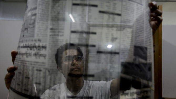 "Graphic designer of Myanmar's weekly newspaper ""Weekly Eleven"" looks at the film of the next morning's edition of the newspaper at midnight in Yangon, Myanmar, Monday, April 2, 2012. Myanmar's opposition icon Aung San Suu Kyi, 66, was elected to parliament Sunday in a historic victory buffeted by the jubilant cheers of supporters who hope her triumph will mark a major turning point in a nation still emerging from a ruthless era of military rule. (AP Photo/Altaf Qadri)"
