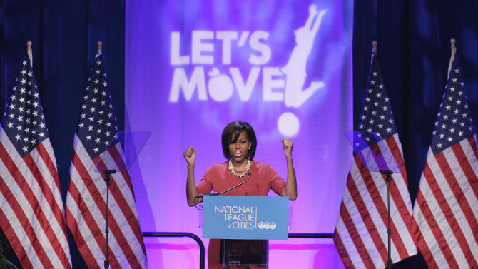 "FILE - In this March 15, 2011, file photo, first lady Michelle Obama gestures while speaking speaks at the National League of Cities Conference about the Let's Move! initiative in Washington. Michelle Obama has a new look, both in person and online, and with the president's re-election, she has four more years as first lady, too. The first lady is trying to figure out what comes next for this self-described ""mom in chief"" who also is a champion of healthier eating, an advocate for military families, a fitness buff and the best-selling author of a book about her White House garden. For certain, she'll press ahead with her well-publicized efforts to reduce childhood obesity and rally the country around its service members. (AP Photo/File)"