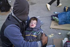 A Syrian refugee man holding his sleeping son, rests…