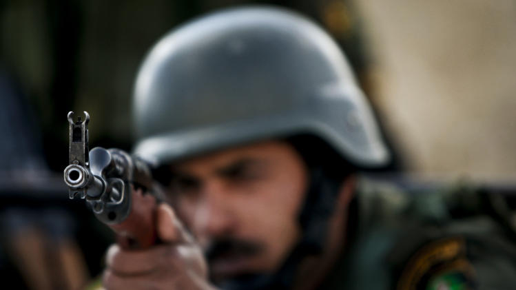 A Palestinian security officer takes aim during a march in support of Palestinian President Mahmoud Abbas, and to celebrate their successful bid to win U.N. statehood recognition the in the West bank city of Bethlehem, Monday, Dec. 17, 2012. (AP Photo/Majdi Mohammed)