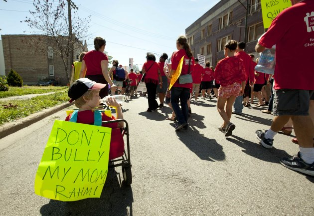 A young boy in a cart is pulled along by his mother at the tail of a group of public school teachers marching on streets surrounding John Marshall Metropolitan High School on Wednesday, Sept. 12, 2012