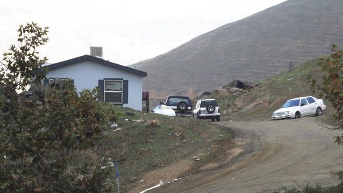 Vehicles sit parked at the compound where three deceased adults and one severely wounded boy were discovered on the Tule River Indian Reservation, in California, Sunday, Dec. 9, 2012. Two adults were found in a fifth-wheel travel trailer next to the home and a third was found in a wooden outbuilding, both not visible in this view. Hector Celaya, 31, is a suspect in the shootings in which three people died and four others, including two young girls, were wounded Saturday, Dec. 8, 2012, on the reservation in the Sierra foothills of California's Central Valley. (AP Photo/Tracie Cone)
