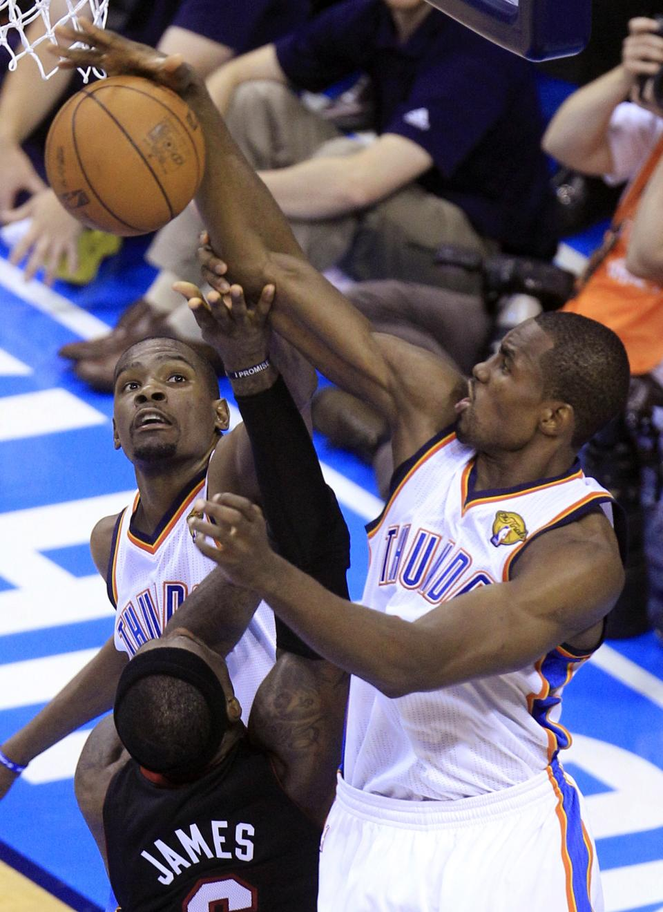 Miami Heat small forward LeBron James  is blocked by Oklahoma City Thunder power forward Serge Ibaka (9) from Republic of Congo as small forward Kevin Durant (35) helps during the second half at Game 2 of the NBA finals basketball series, Thursday, June 14, 2012, in Oklahoma City. (AP Photo/Sue Ogrocki)