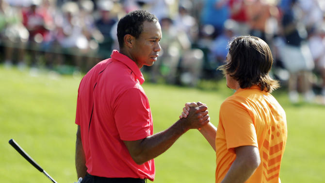 Tiger Woods, left, shakes hands with Rickie Fowler after making a birdie putt on the 18th hole during the final round of the Memorial golf tournament, Sunday, June 3, 2012, in Dublin, Ohio. Woods birdied three of his last four holes to win the Memorial and match tournament host Jack Nicklaus with his 73rd title on the PGA Tour. (AP Photo/Jay LaPrete)