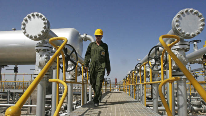 """In this Tuesday, April 15, 2008 file photo, Iranian oil technician Majid Afshari makes his way to the oil separator facilities in Iran's Azadegan oil field southwest of Tehran. Iran has stored up imported goods and hard currency for a """"battle"""" against EU sanctions targeting the country's vital oil sector that went into effect Sunday, officials said. They acknowledged though that the measures, which aim at pressuring the Islamic Republic over its nuclear program, may cause economic disruptions. (AP Photo/Vahid Salemi, File)"""