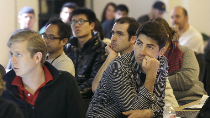 In this Saturday, Feb. 8, 2014 photo, Segah Meer, right, and other participants listen to speakers during the FinCapDev San Francisco Hackathon in San Francisco. A record 1,500 hackathons around the world are planned for this year, up from just a few dozen in 2010, and their focus is broadening from developing lucrative apps to solving problems with coding for an array of issues including dental, fashion, immigration, transgender and social justice. (AP Photo/Jeff Chiu)