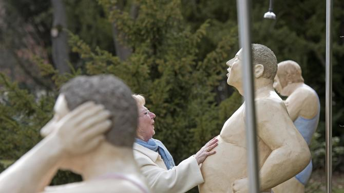 A woman touches a sculpture of the installation 'Showering' during the press preview at the exhibition 'Ordinary People' by Christel Lechner in the Baroque garden of the Lichtenwalde castle near Chemnitz, eastern Germany, Friday, March 27, 2015. For many years the German artist Christel Lechner has been working on a series of engaging sculptures entitled 'Alltagsmenschen - Ordinary People'. The statues have been installed as public art in real world settings at various nondescript outdoor locations. The exhibition starts on March 28 and last until Nov. 1, 2015. (AP Photo/Jens Meyer)
