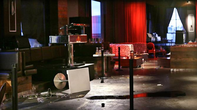 The interior of the Munchbar, where tables are seen overturned and debris strewn about, is photographed Monday, Dec. 24, 2012, in Bellevue, Wash. A 30-year-old Seattle man was killed and another man wounded in a shooting at the crowded bar earlier in the morning about 10 miles east of Seattle. (AP Photo/Elaine Thompson)