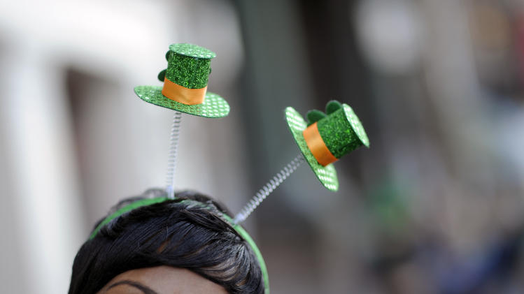 Krystal Thomas of Atlanta parties on River Street while wearing a shamrock head-band during the 189th St. Patrick's Day celebration, Friday Mar. 16, 2013 in Savannah, Ga. (AP Photo/Stephen Morton)