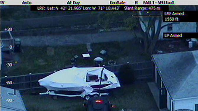 This Friday, April 19, 2013 image made available by the Massachusetts State Police shows a police vehicle probing the boat where 19-year-old Boston Marathon bombing suspect, Dzhokhar Tsarnaev, was hiding in Watertown, Mass. He was pulled, wounded and bloody, from the boat parked in the backyard of a home in the Greater Boston area. (AP Photo/Massachusetts State Police)