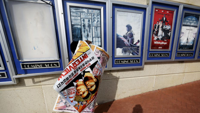 "A poster for the movie ""The Interview"" is carried away by a worker after being pulled from a display case at a Carmike Cinemas movie theater, Wednesday, Dec. 17, 2014, in Atlanta. Georgia-based Carmike Cinemas has decided to cancel its planned showings of ""The Interview"" in the wake of threats against theatergoers by the Sony hackers. (AP Photo/David Goldman)"