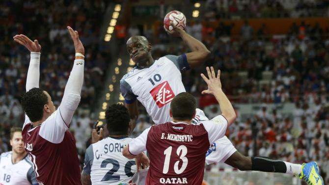 Nyokas of France shoots over Benali and Memisevic of Qatar during their final match of the 24th Men's Handball World Championship in Doha