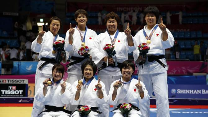 Japan's team pose with their gold medals after defeating South Korea's team in their women's team gold medal judo contest in Incheon