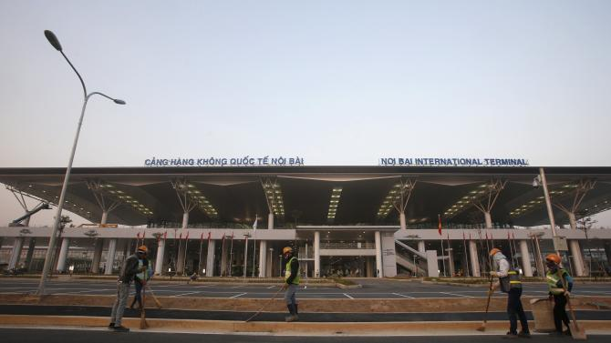 Workers sweep the road ahead of the opening of the new terminal two wing at Noi Bai international airport in Hanoi