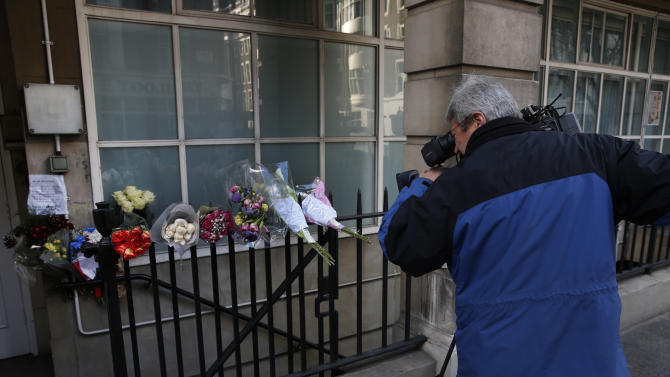 A news cameraman films flower tributes to late nurse Jacintha Saldanha outside the residential apartments of the the King Edward VII hospital where she was found dead, in central London, Monday, Dec. 10, 2012. Australian radio hosts managed to impersonate Queen Elizabeth II and Prince Charles and received confidential information about the Duchess of Cambridge's medical condition, in a hoax phone call to the hospital where the pregnant Duchess was staying and which was broadcast on-air. The controversial prank took a dark twist three days later with the death of Saldanha, a 46-year-old mother of two, who was duped by the DJs despite their Australian accents. (AP Photo/Lefteris Pitarakis)