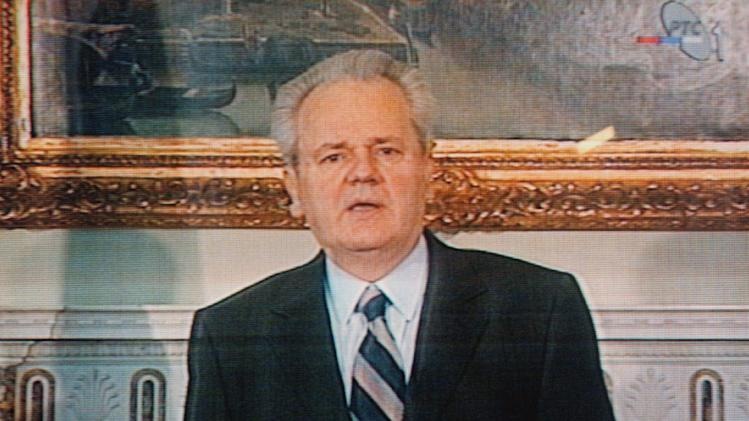 """FILE - In this March 24, 1999, file photo, taken from television, former Yugoslav President Slobodan Milosevic addresses the nation from Belgrade, Serbia. Caption at bottom translates, """"Slobodan Milosevic President of the Federal Republic of Yugoslavia."""" NATO war planes were hitting tanks with deadly precision in Serbia, aiming to degrade a despot's army and empower the ragtag rebel force, which appears to echo the air strikes on the forces of Libyan leader Moammar Gadhafi, although in Libya there is no endgame in sight, yet. (AP Photo/Darko Vojinovic, File)"""