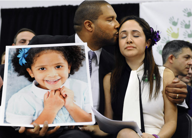 Jimmy Greene, left, kisses his wife Nelba Marquez-Greene as he holds a portrait of their daughter, Sandy Hook School shooting victim Ana  Marquez-Greene at a news conference at Edmond Town Hall in New