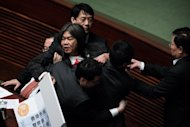 Hong Kong lawmaker Leung Kwok-hung is escorted out of the legislative chamber after disrupting a policy address by Hong Kong Chief Executive Leung Chun-ying (not in picture) on January 16, 2013. Leung has unveiled a raft of populist policies with an emphasis on tackling the city&#39;s housing crisis, as he aimed to hush critics&#39; repeated calls to step down