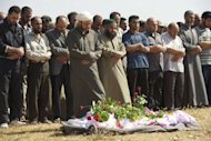 Syrian mourners pray over the body of a member of the Free Syrian Army during his funeral in the restive province of Homs, on June 22