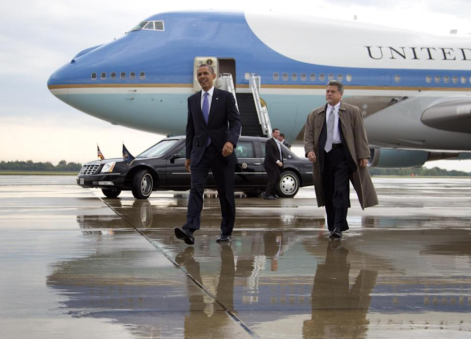 President Barack Obama walks across the wet tarmac to greets people as he arrives on Air Force One at Rickenbacker International Airport in Columbus, Ohio,  Tuesday, Aug. 21, 2012. (AP Photo/Carolyn Kaster)