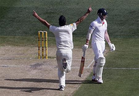 Australia's Johnson runs past England's Stokes after he dismissed him for 14 runs during the first day of the fourth Ashes cricket test at the Melbourne cricket ground