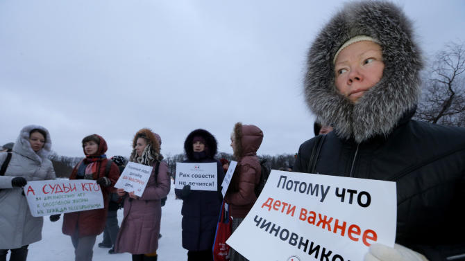 """A demonstrator holds a poster reading """"Children are more important than officials"""" during a protest against plans to shut down City Hospital No. 31 in St. Petersburg, Russia, Wednesday, Jan. 23, 2013. Some 1,500 thousand people gathered for a rally against plans to shut a clinic specialized in treating children with cancer in order to turn it into a medical center for the nation's top judges. The authorities intention to turn City Hospital No. 31 into a clinic that would exclusively serve judges of Russia's top courts, which are being relocated to St.Petersburg from Moscow, has caused a strong public dismay. On Wednesday, St.Petersburg Governor's office said that the hospital will continue to serve patients as before and there is no plan to change its location or profile.  (AP Photo/Dmitry Lovetsky)"""