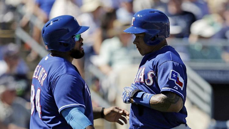 Texas Rangers' Prince Fielder, left, and Michael Choice celebrate after scoring on a hit by Adam Rosales during the third inning of an exhibition spring training baseball game against the Texas Rangers, Sunday, March 9, 2014, in Peoria, Ariz. (AP Photo/Darron Cummings)