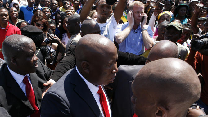 Firebrand politician Julius Malema, center, is escorted by his bodyguards to address supporters after appearing at the Magistrate's Court in Polokwane, South Africa, Wednesday, Sept.  26, 2012, on charges of money laundering in connection with an improper government tender awarded to a company his family trust partly owns. (AP Photo/Themba Hadebe)