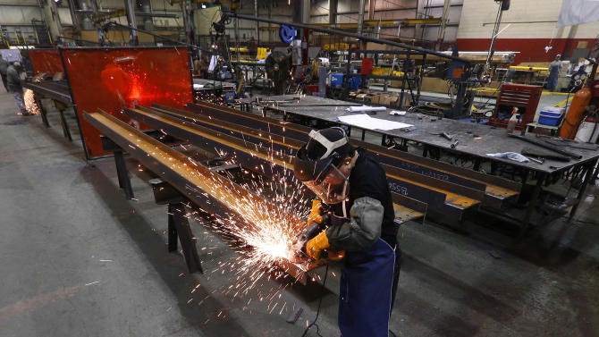 In this Thursday, Jan. 23, 2014 photo, Jesus Rodriguez grinds steel at the IDEAL Group in Detroit. The Institute for Supply Management reports on U.S. manufacturing activity in February on Monday, March 3, 2014. (AP Photo/Paul Sancya)