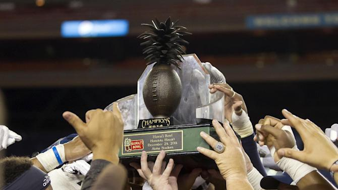 The Rice football team holds up the Hawaii Bowl trophy after the Hawaii Bowl NCAA college football game against Fresno State, Wednesday, Dec. 24, 2014, in Honolulu