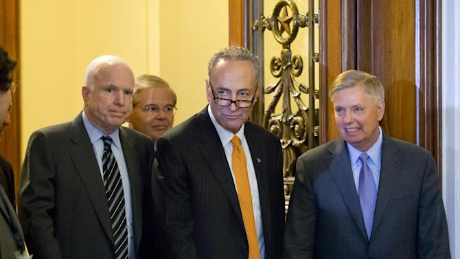 """Members of the bipartisan """"Gang of Eight"""" who crafted the immigration reform bill, Sen. Chuck Schumer, D-N.Y., center, flanked by Sen. John McCain, R-Ariz., left, and Sen. Lindsey Graham, R-S.C., leave the floor after final passage in the Senate, at the Capitol in Washington, Thursday, June 27, 2013. Sen. Robert Menendez, D-N.J., follows at rear. In remarks to reporters, Sen. Lindsey Graham, a conservative Republican, praised the leadership of Democrat Chuck Schumer, saying """"Senator Schumer's a worthy successor to Ted Kennedy."""" (AP Photo/J. Scott Applewhite)"""