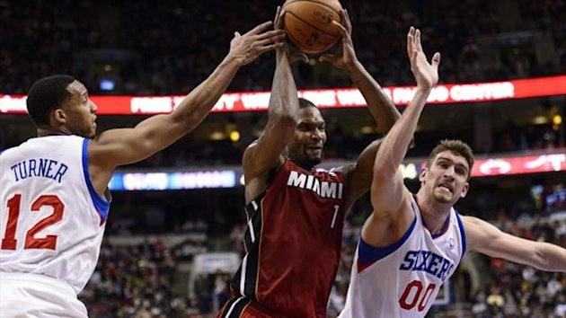 Miami Heat center Chris Bosh (1) fights through Philadelphia 76ers guard Evan Turner (12) and center Spencer Hawes (00) (Reuters)